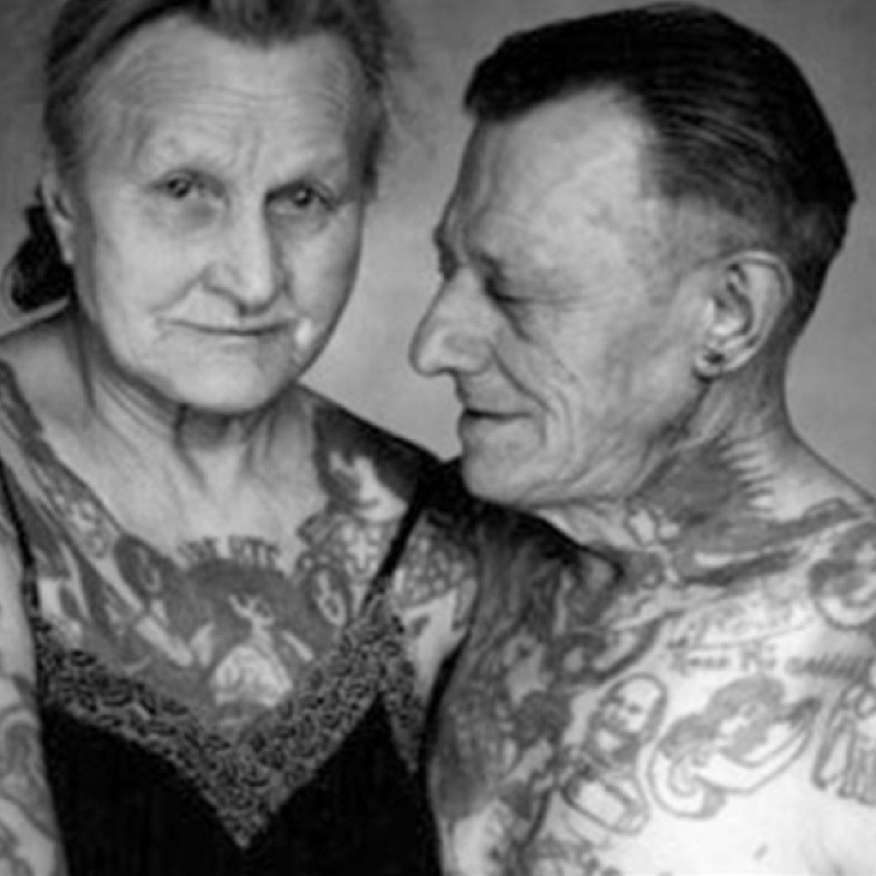 Old man and woman hugging with tattoos.